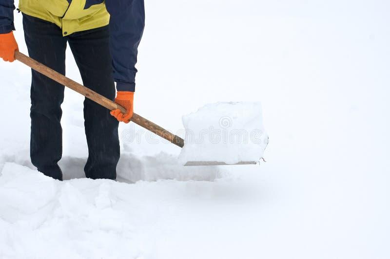 Mens die een weg van sneeuw graaft stock foto