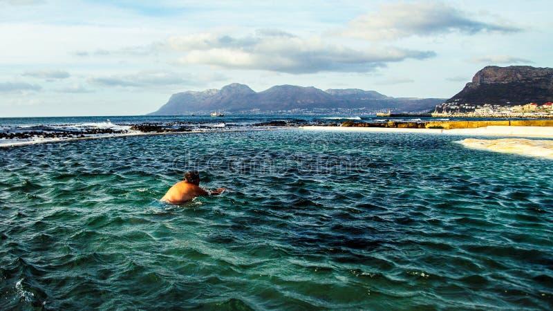 Mens die in een wind-swept getijdepool tegen bergachtergrond zwemmen stock foto