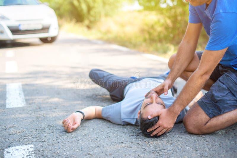 Mens die eerste hulp in autoongeval geven stock afbeelding