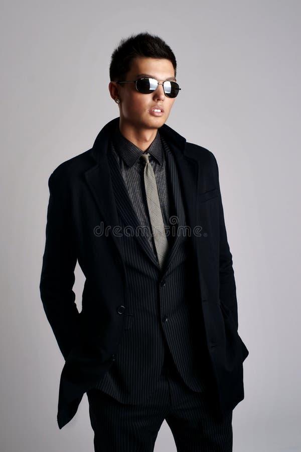 Mens die elegante zwarte kostuum en zonnebril draagt stock afbeelding