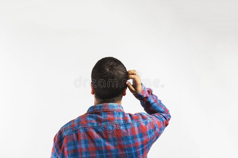 mens die en aan een muur denken de kijken, Vergeetachtige afwezige gelete op mens probeert om iets, achtermening te herinneren stock afbeeldingen