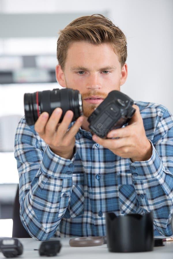 Mens die en digitale camera schoonmaken herstellen royalty-vrije stock afbeeldingen