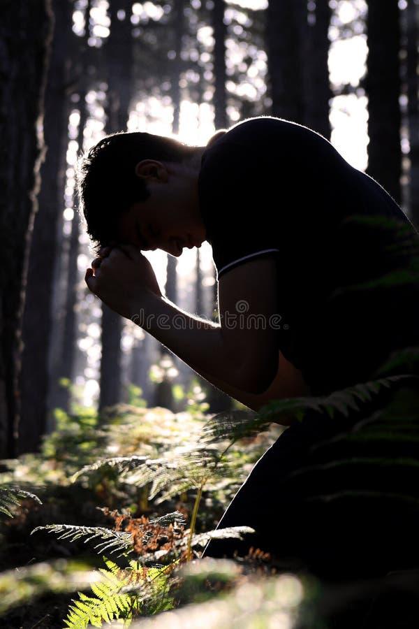 Mens die en in het bos knielt bidt