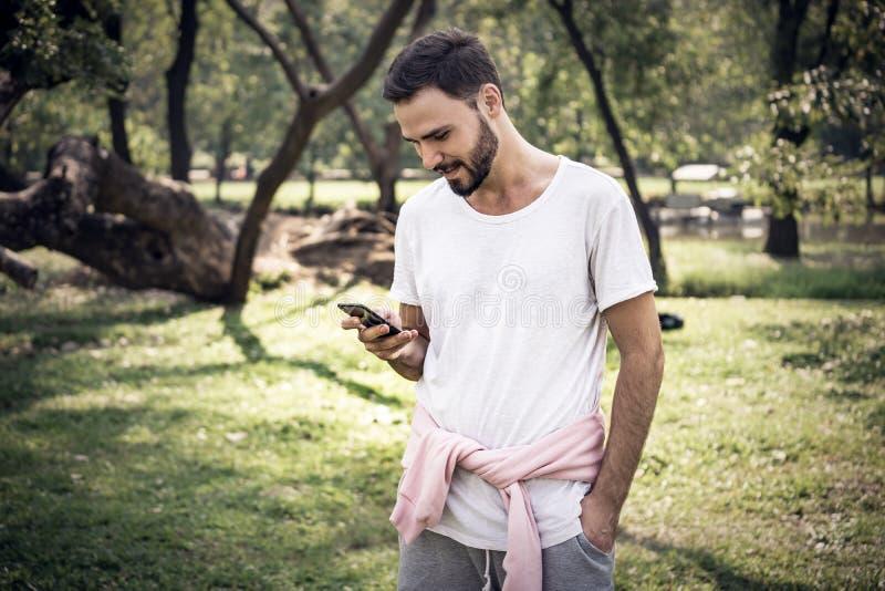 Mens die en zijn cellphone in openbaar park glimlacht gebruikt stock afbeeldingen