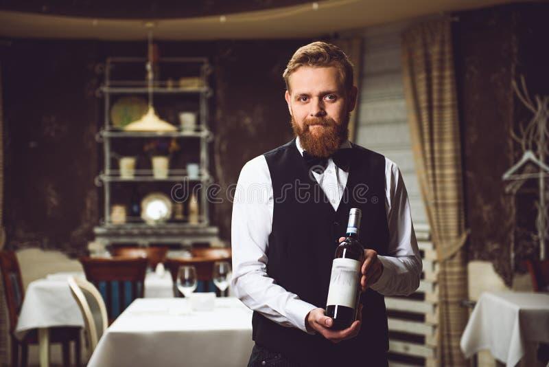 Mens die fles wijn voorstellen stock fotografie