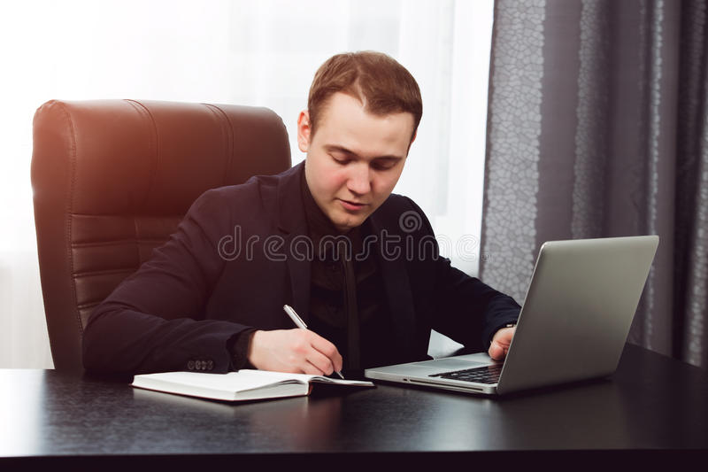 Mens die in formele kleding nota's schrijven aan zijn notitieboekje stock fotografie