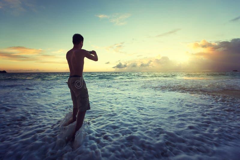 mens die foto's van zonsondergang op tropisch strand nemen stock afbeelding