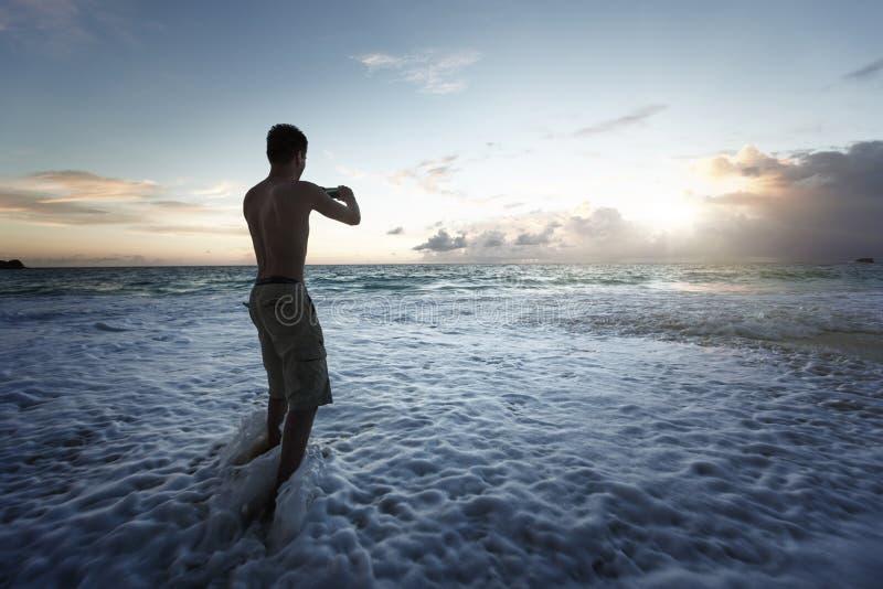 Mens die foto's van zonsondergang op tropisch strand nemen door smartphone royalty-vrije stock afbeelding