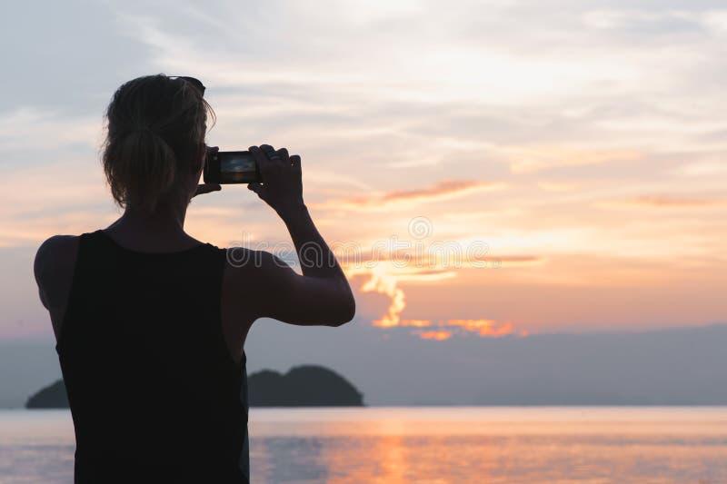 Mens die foto in schilderachtig overzees landschap nemen bij zonsondergang stock fotografie