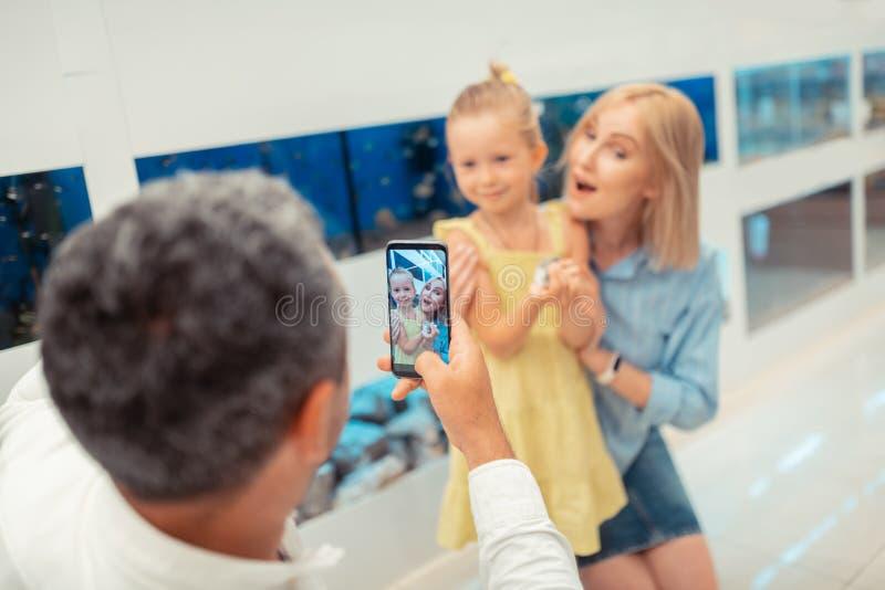 Mens die foto van dochter en de hamster van de vrouwenholding nemen stock afbeeldingen