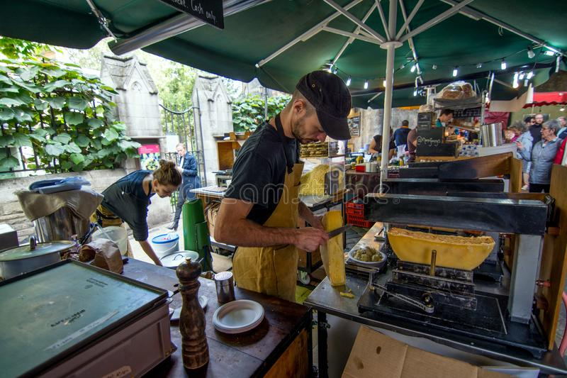 Mens die frieten met gesmolten kaas in één van de borrow van Londen markt voorbereiden stock afbeeldingen