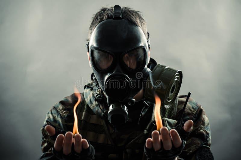 Mens die gasmasker met brand op handen dragen royalty-vrije stock afbeeldingen