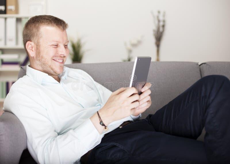 Mens die gelukkig glimlachen aangezien hij zijn tablet leest stock afbeelding