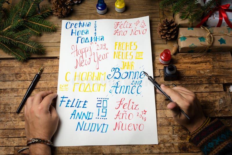 Mens die gelukkig nieuw jaar in verschillende talen schrijven stock foto