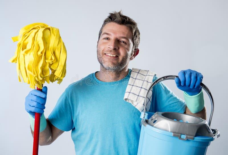 Mens die gelukkige het doen huis het schoonmaken holdingszwabber en emmerwas glimlachen stock afbeeldingen