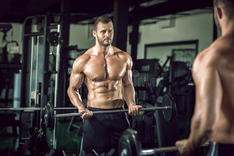 Mens die gewichtheffen in gymnastiek doen royalty-vrije stock foto's