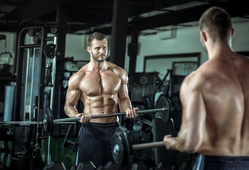 Mens die gewichtheffen in gymnastiek doen royalty-vrije stock afbeelding