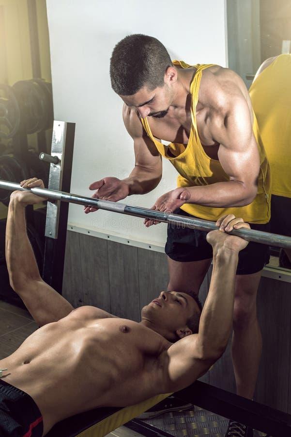 Mens die gewichtheffen met persoonlijke trainer doen royalty-vrije stock foto