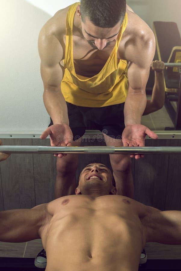 Mens die gewichtheffen met persoonlijke trainer doen royalty-vrije stock fotografie