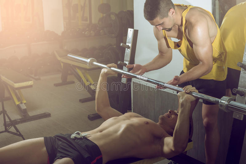 Mens die gewichtheffen met persoonlijke trainer doen stock afbeeldingen