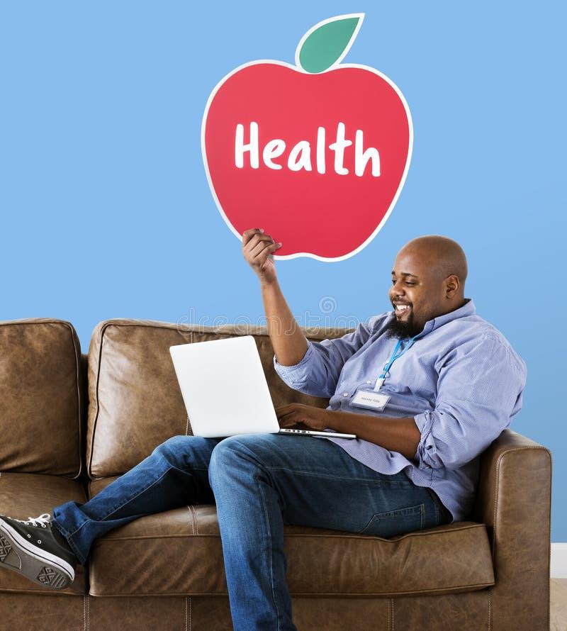 Mens die gezond appelpictogram op laag tonen royalty-vrije stock afbeeldingen