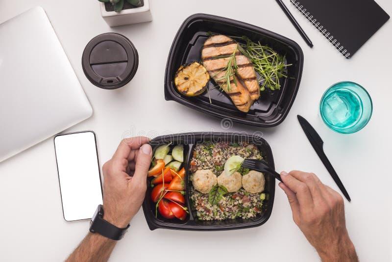Mens die gezond voedsel met geroosterde vissen in bureau eten tijdens lunch royalty-vrije stock afbeeldingen