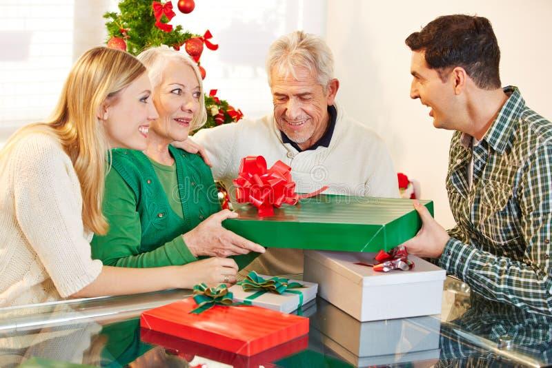 Mens die gift geven aan zijn moeder bij Kerstmis royalty-vrije stock fotografie