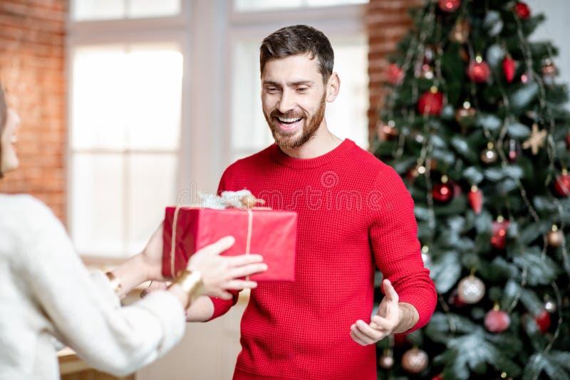 Mens die gift het vieren Nieuwjaarvakantie thuis ontvangen stock foto
