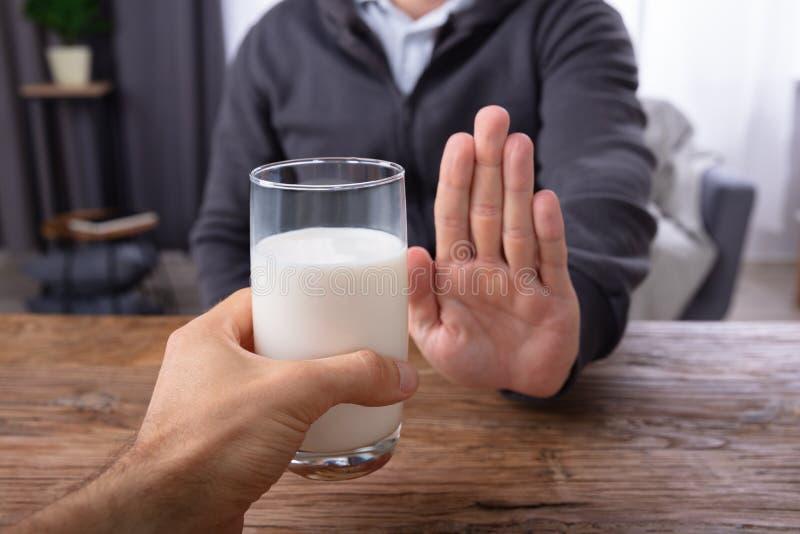 Mens die Glas Melk weigeren dat door Persoon wordt aangeboden stock foto
