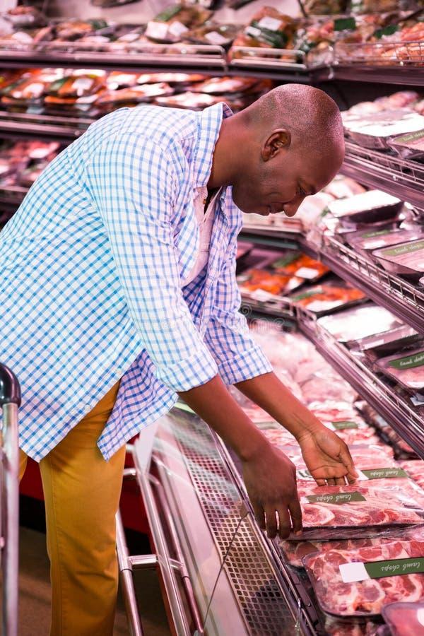 Mens die goederen in kruidenierswinkelsectie bekijken terwijl het winkelen royalty-vrije stock afbeelding