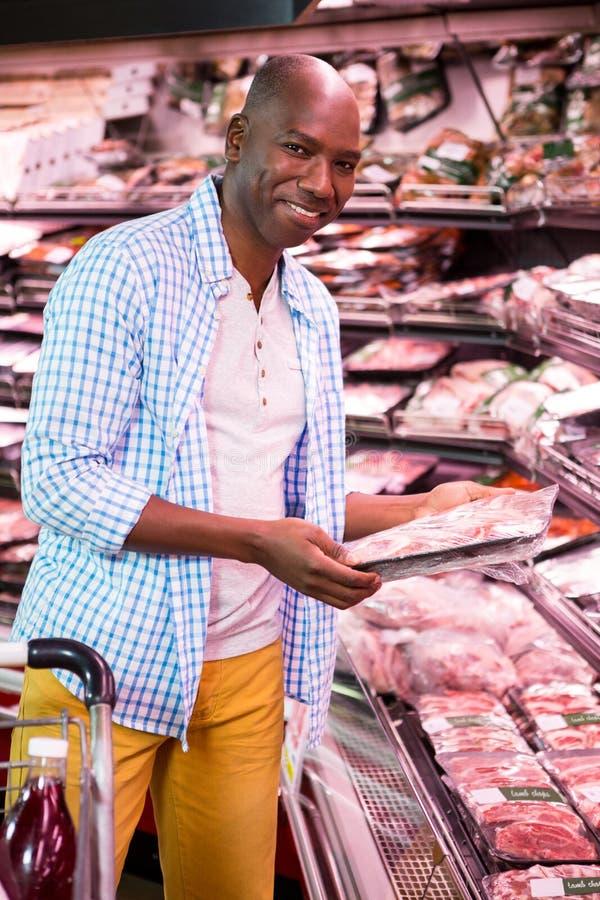 Mens die goederen in kruidenierswinkelsectie bekijken terwijl het winkelen in supermarkt stock afbeelding