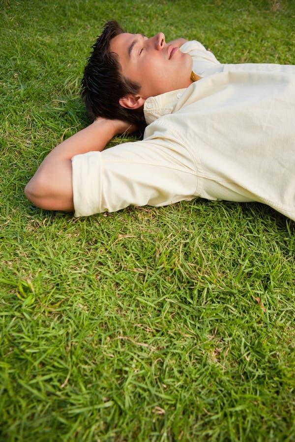 Mens die in gras met zijn gesloten ogen ligt royalty-vrije stock afbeeldingen