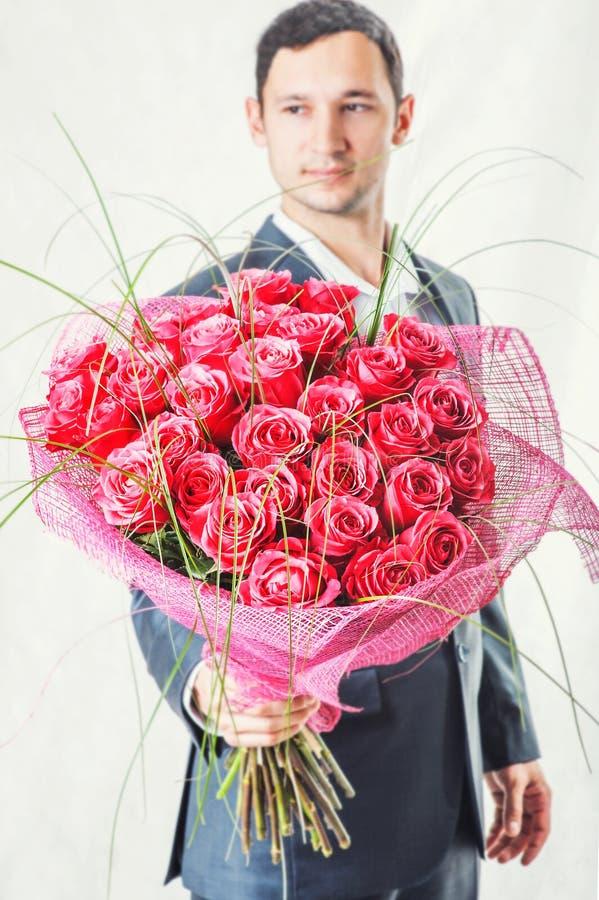 Mens die grote bos van rode rozen houden royalty-vrije stock fotografie