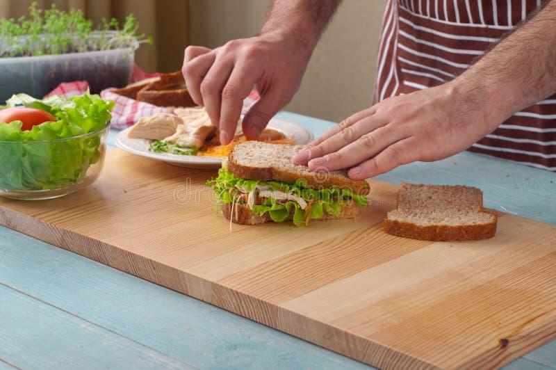Mens die grote sandwich met kip koken stock afbeeldingen