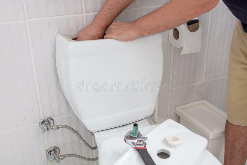 Mens die handen gebruiken die toiletreservoir herstellen stock fotografie
