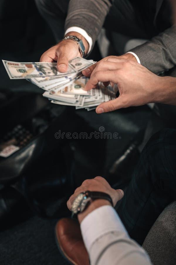 Mens die handhorloge en wit overhemd dragen die uitbetaling ontvangen royalty-vrije stock foto's