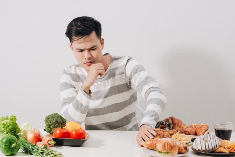 Mens die harde keus tussen gezond en ongezond voedsel hebben stock fotografie