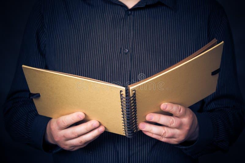 Mens die het boek van de overhemdslezing dragen stock foto's