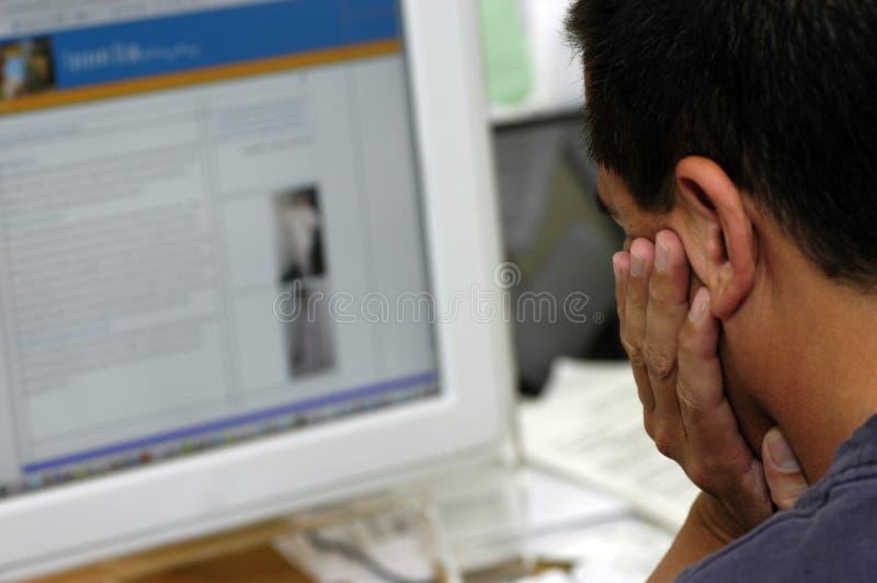 Mens die het computerscherm bekijkt stock afbeeldingen