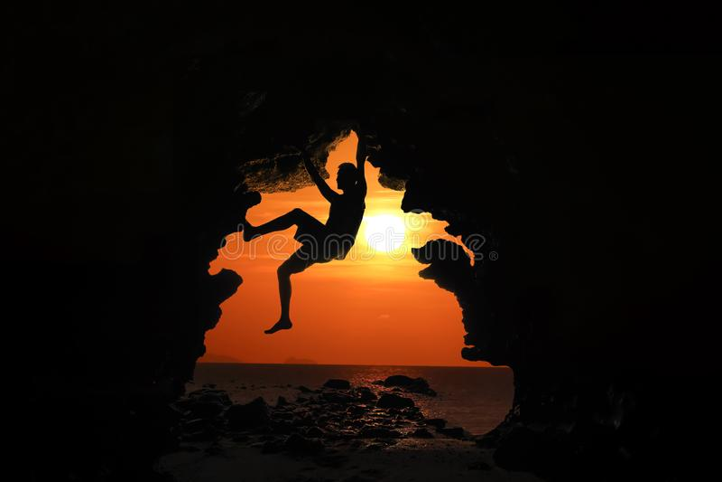Mens die in het hol door het overzees met rode hemel en zonsondergang beklimmen royalty-vrije stock foto's