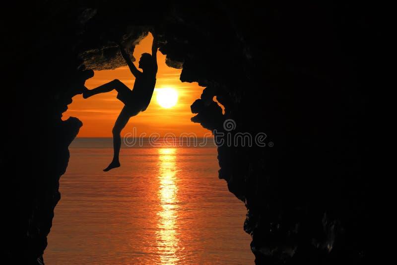 Mens die in het hol door het overzees met rode hemel en zonsondergang beklimmen royalty-vrije stock afbeeldingen