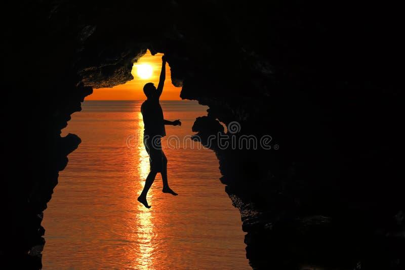 Mens die in het hol door het overzees met rode hemel en zonsondergang beklimmen stock fotografie