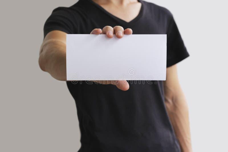 Mens die het lege witte boekje van de vliegerbrochure tonen Pamfletpresentatie De handen van de pamfletgreep De mens toont duidel stock afbeeldingen