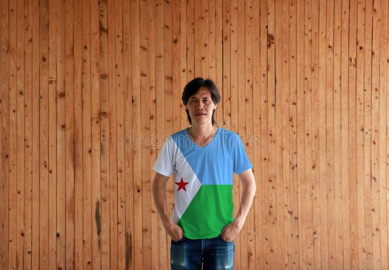 Mens die het overhemd van de de vlagkleur van Djibouti dragen en zich met twee de bevinden dient broekzakken op de houten muurach stock foto
