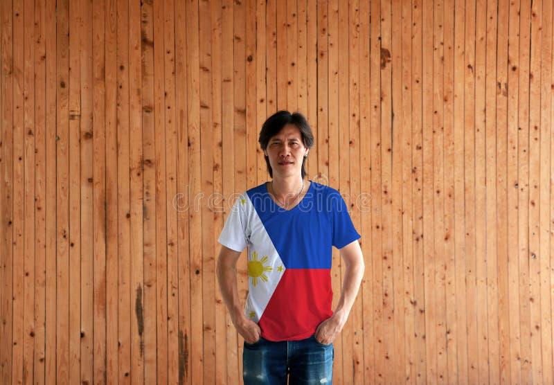 Mens die het overhemd van de de vlagkleur van Filippijnen dragen en zich met twee de bevinden dient broekzakken op de houten muur royalty-vrije stock foto