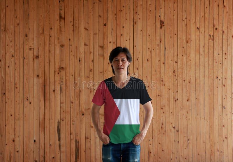 Mens die het overhemd van de de vlagkleur van Palestina dragen en zich met twee de bevinden dient broekzakken op de houten muurac stock afbeelding