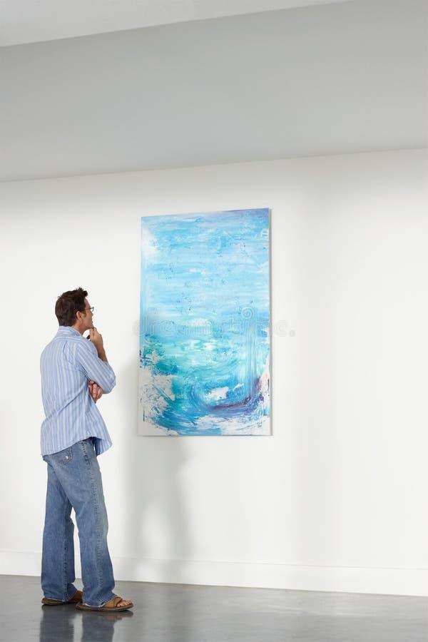 Mens die het Schilderen in Art Gallery waarnemen royalty-vrije stock afbeelding