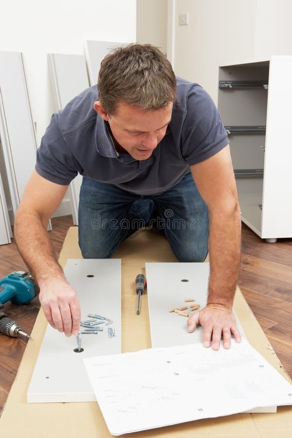 Mens die het Vlakke Meubilair van het Pak assembleert stock foto's