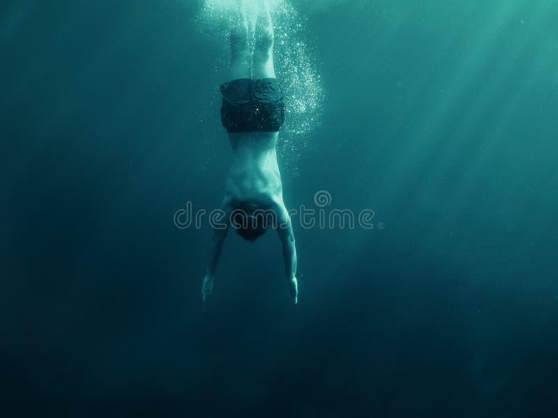 Mens die in het water springen Onderwater schot Vakantie, sporten en actief levensstijlconcept stock fotografie
