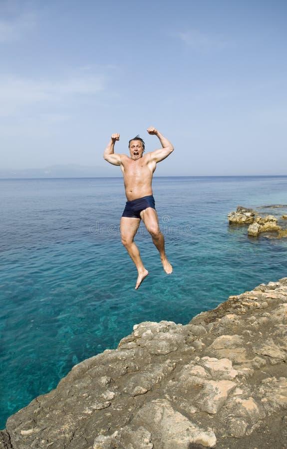 Mens die in het water springt stock afbeeldingen